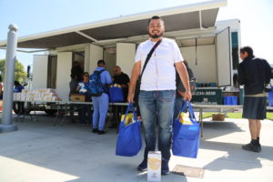 College student with groceries in front of Mobile Food Pantry