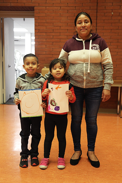 Mother and her two children, a smiling boy and girl, holding up their art work.