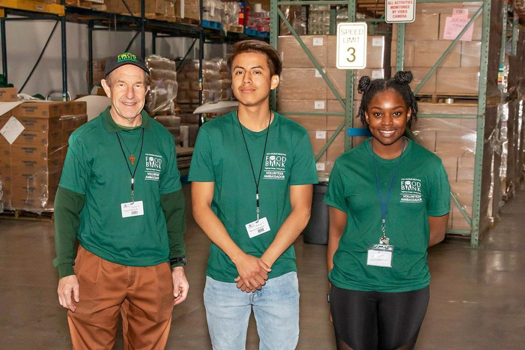three people standing in warehouse smiling