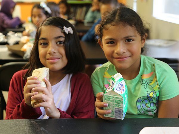 Two young girls smiling at the Summer Lunch Program