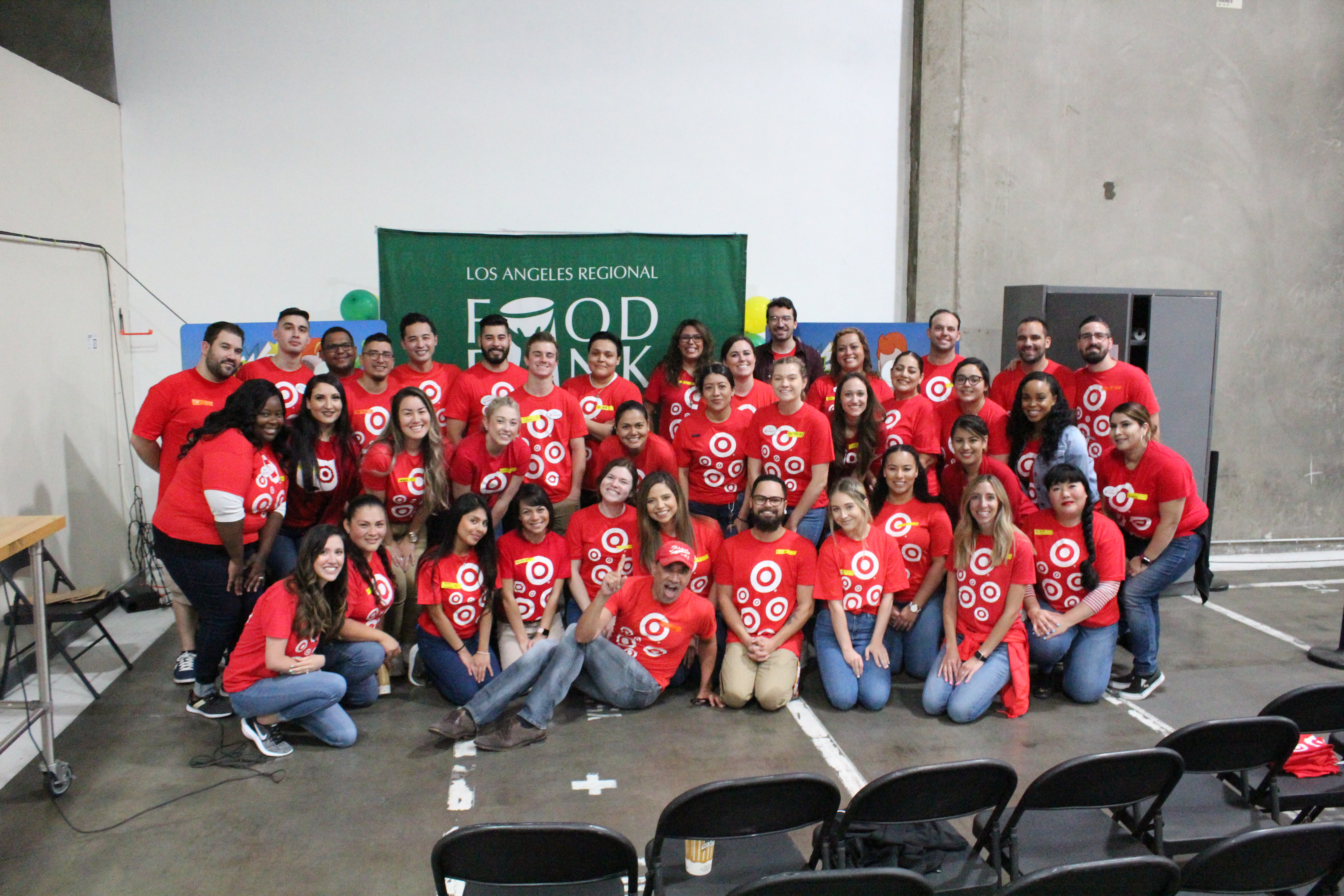 Target volunteers, wearind red shirts, at the LA Regional Food Bank - smiling.