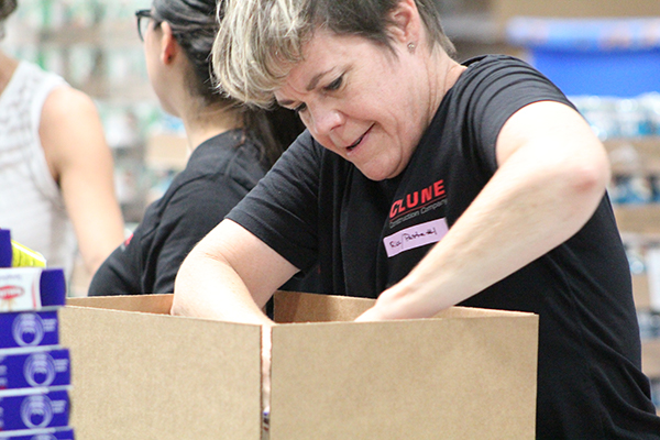 A Clune Construction volunteer packing boxes.
