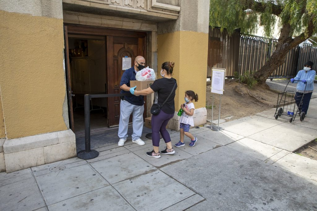 A volunteer hands food kits to a mother and her child at a walk-up food distribution.