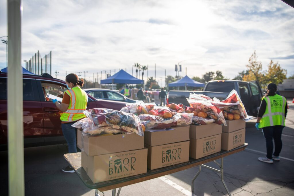 Food kits and fresh produce are stacked for distribution at a drive-through food giveaway hosted by the LA Regional Food Bank at Citrus College, CA.