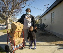 Mrs. Carson and her 2-year-old granddaughter take a picture next to food kits they received at a drive-through food distribution.
