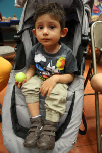 Young boy in stroller holding an apple.