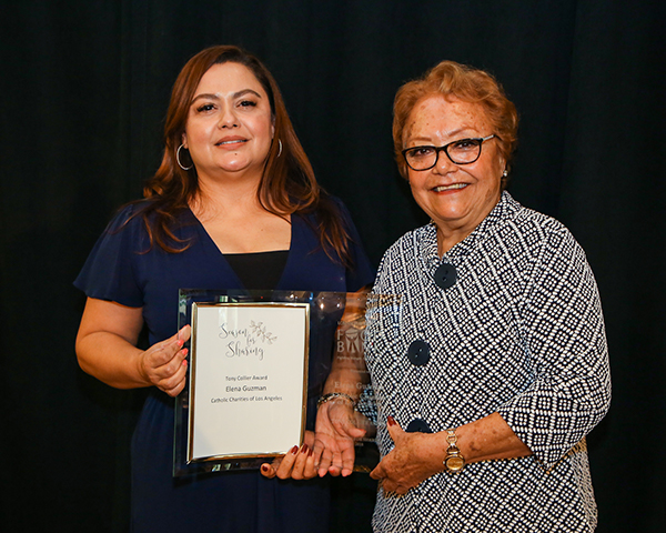 Elizabeth Cervantes (r) presents Elena Guzman with the Tony Collier Award at Season for Sharing Luncheon