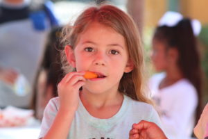 Young student eating a carrot