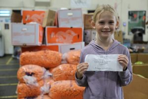 Maggie Williamson holds birthday check in front of carrots