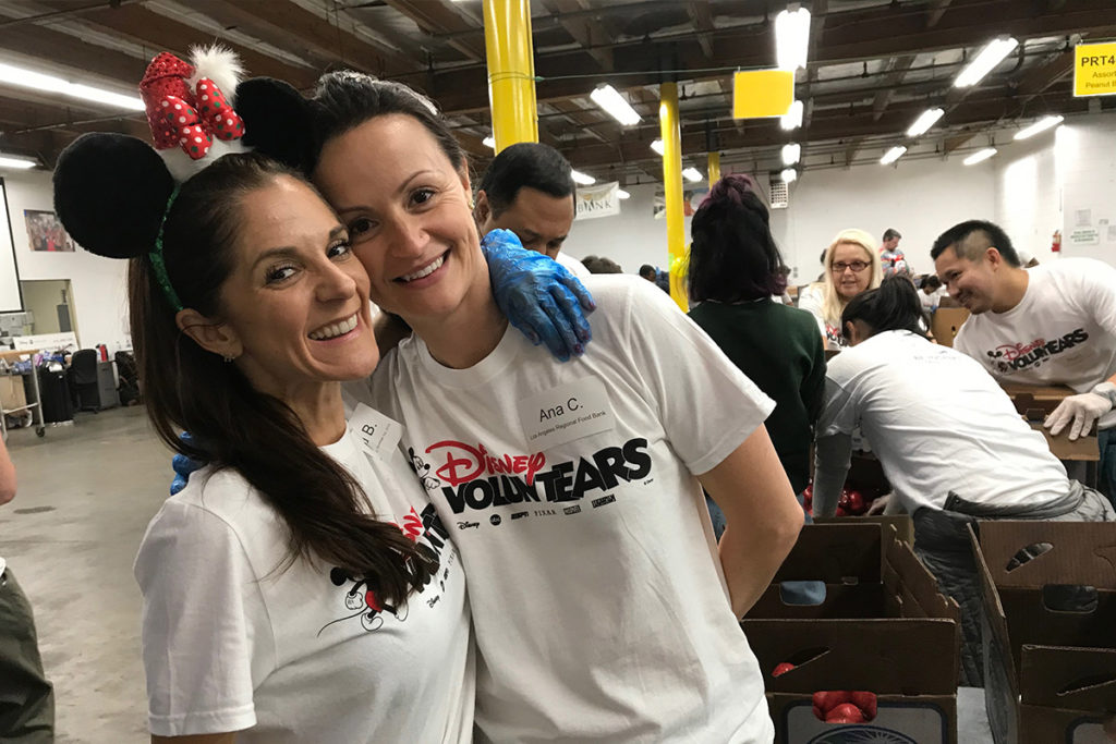 two volunteers smiling in warehouse