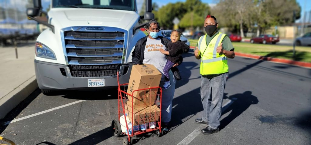 A LA Regional Food Bank employee helps a food recipient and her granddaughter with food boxes at a distribution.